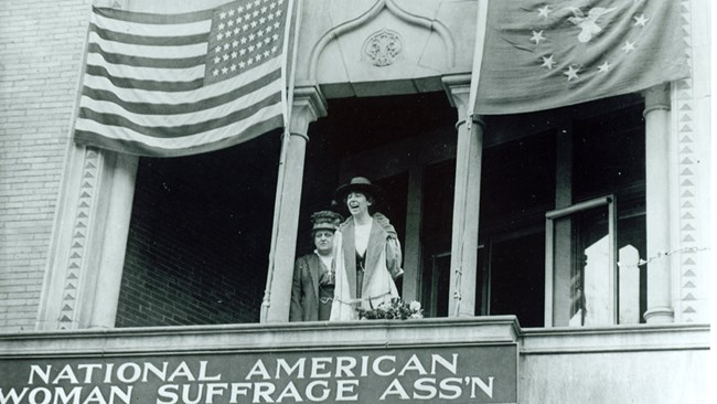 Jeannette Rankin on the balcony of NAWSA headquarters. Carrie Chapman Catt stands beside her