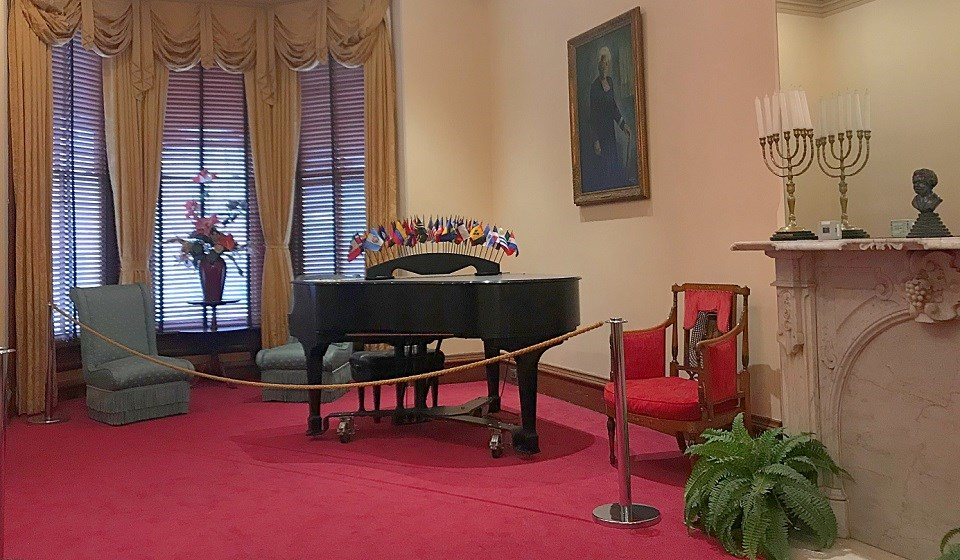 Parlor with a piano, red carpet, fireplace, chandelier, and painting of Mary McLeod Bethune