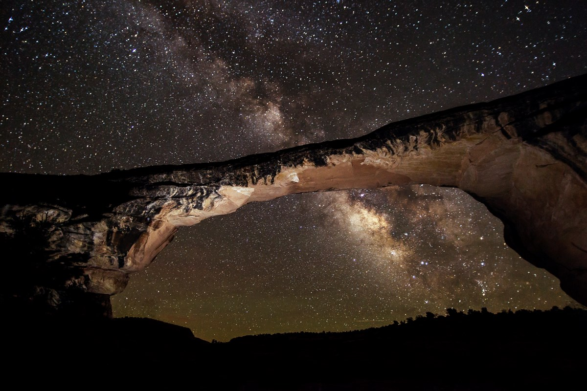 Dark sky full of stars above and through a land bridge.