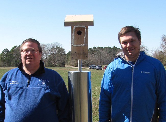 Two men in blue jackets stand next to a bluebird house.