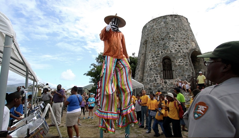 Carnival performer on stilts walking through a crowd near a stone tower