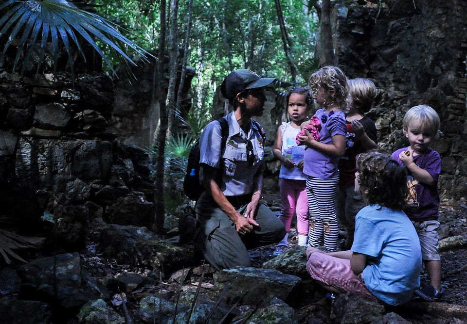 Ranger with a group of kids in a tropical forest