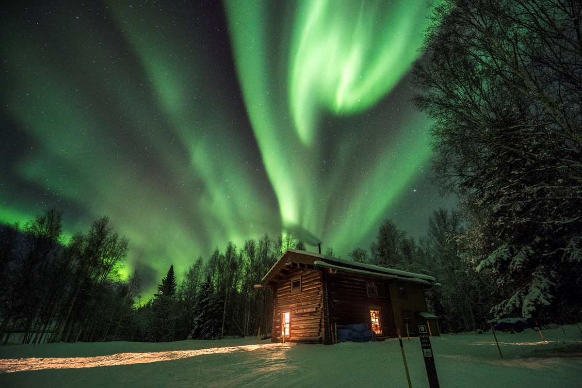 Northern lights over a cabin in the snowy woods