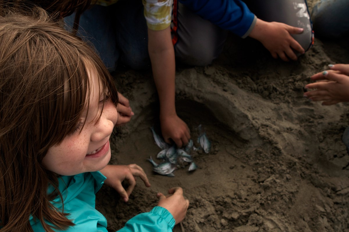 From above, a girl smiles as she sits around a hole dug in the sand.