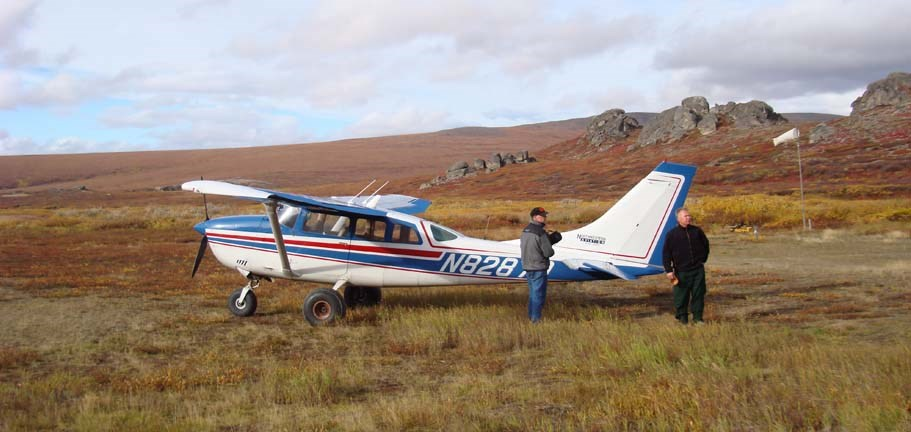 Two men with a small airplane near Serpentine Hot Springs in the fall