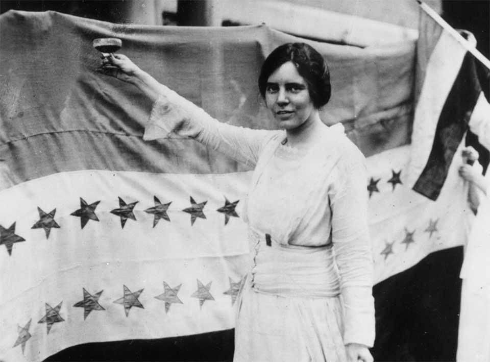 Alice Paul raises glass in front of Victory Star Banner