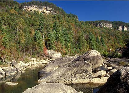 Cliffs of the Big South Fork River gorge tower above huge boulders in the river.