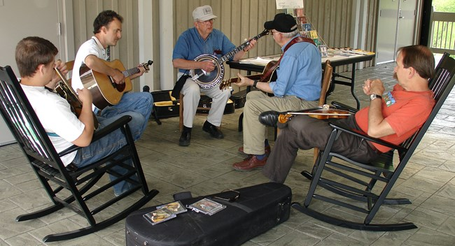 A group of 5 musicians playing guitars, banjo, mandolin and fiddle.