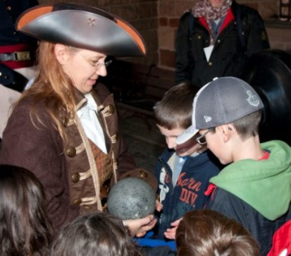A ranger dressed as a privateer answers the questions of eager children.