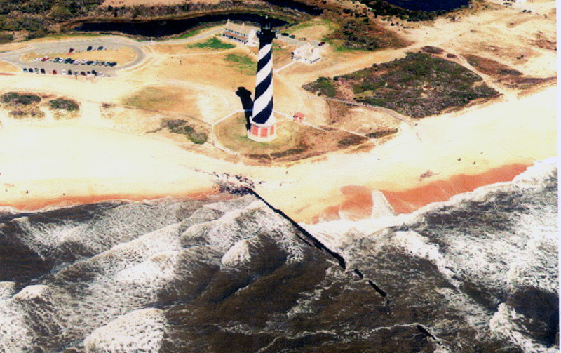 An aerial photograph shows the Cape Hatteras Lighthouse very close to the ocean waves.