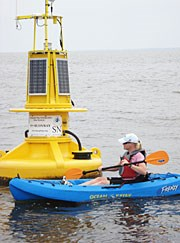A kayaker paddles in front of a NOAA buoy