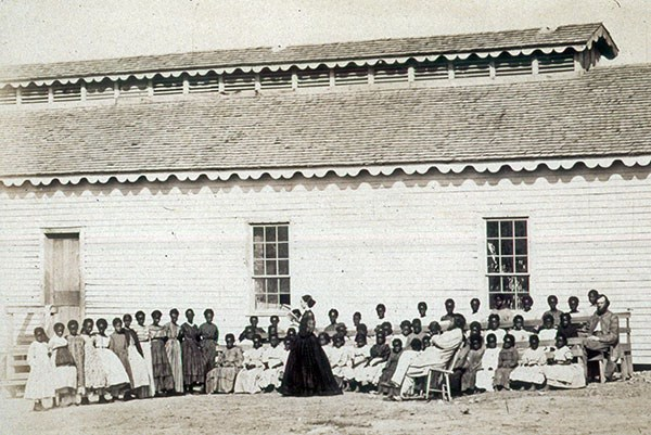 A school teacher reads to her class outside the school house