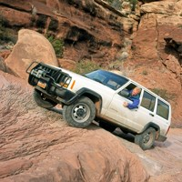A white Jeep drives up a steep slope