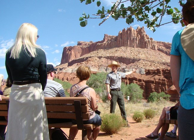 a ranger presenting a program to visitors with sandstone cliffs as a backdrop