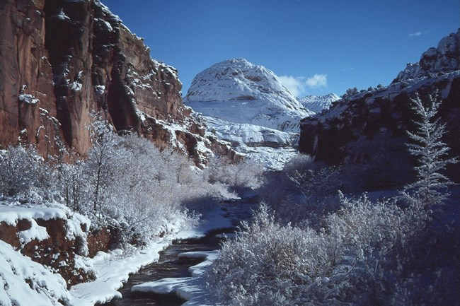 White sandstone dome covered in snow, with red cliffs and a river with snowy banks in foreground.