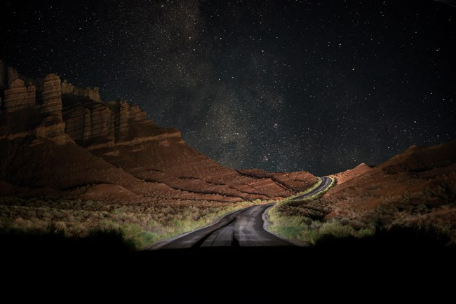 Blacktop road at night, curving between red hills and cliffs, underneath the Milky Way.