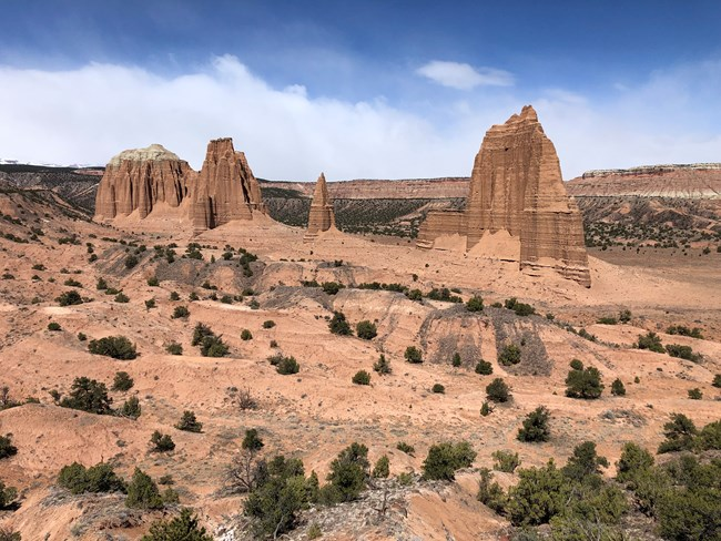 Tall, narrow monoliths of sedimentary rock rising from the ground, with blue sky and clouds in the background.