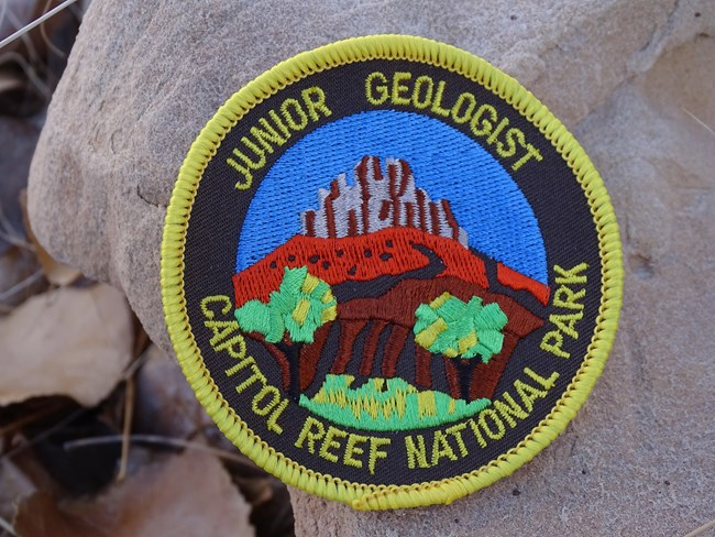 Colorful patch that says Junior Geologist Capitol Reef National Park, on a tan rock.