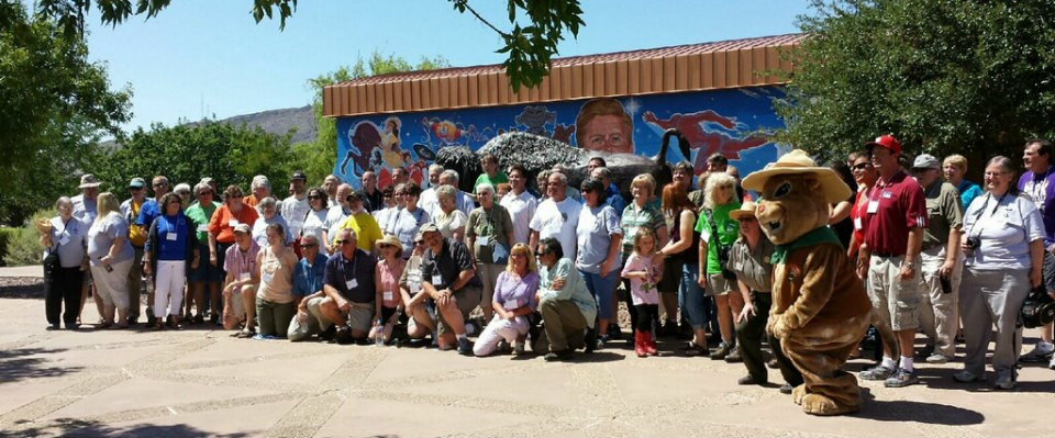 A large group of people pose for photo with squirrel mascot.