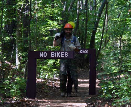 Hiker on trail through forest showing design of new bike barriers.