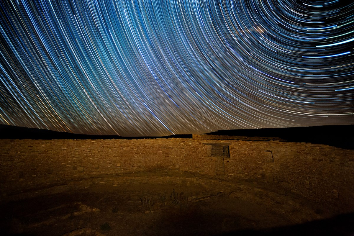 Star trails over a masonry wall.