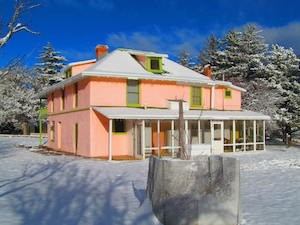 A colorful ranch house dusted in snow