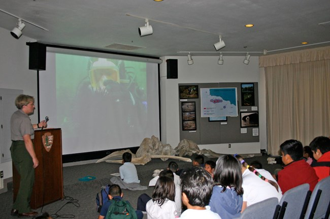Park ranger talking to students looking at screen with diver.