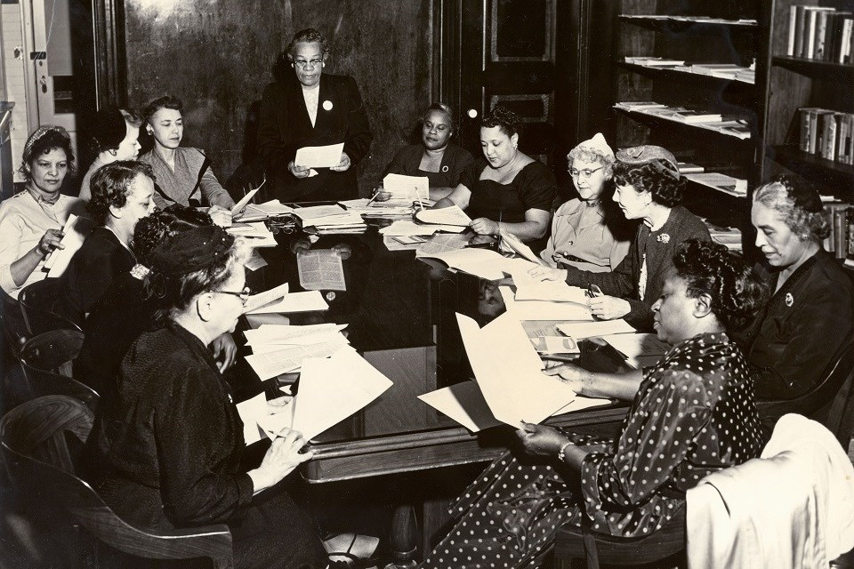 Historical black and white photo of a group of women sitting around a table