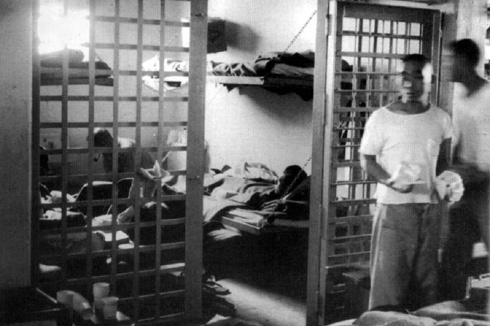 Historic black and white photo of several people in a jail cell with their personal belongings
