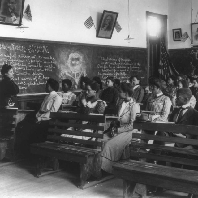 19th century African American students listen to African American teacher in classroom