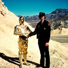 A park ranger stands next to a gold robot, shaking hands, in the desert.