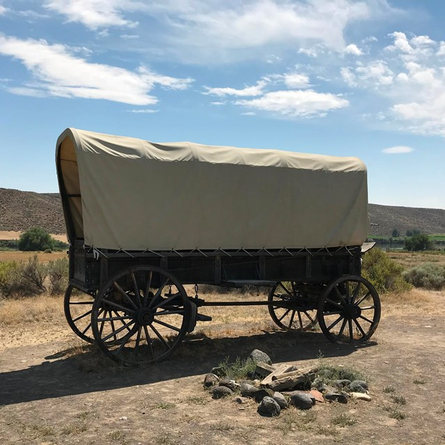 A large covered wagon in a flat desert.