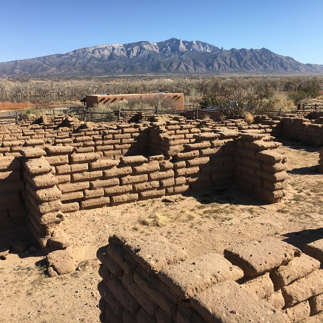 Ruined adobe walls with distant desert mountains.