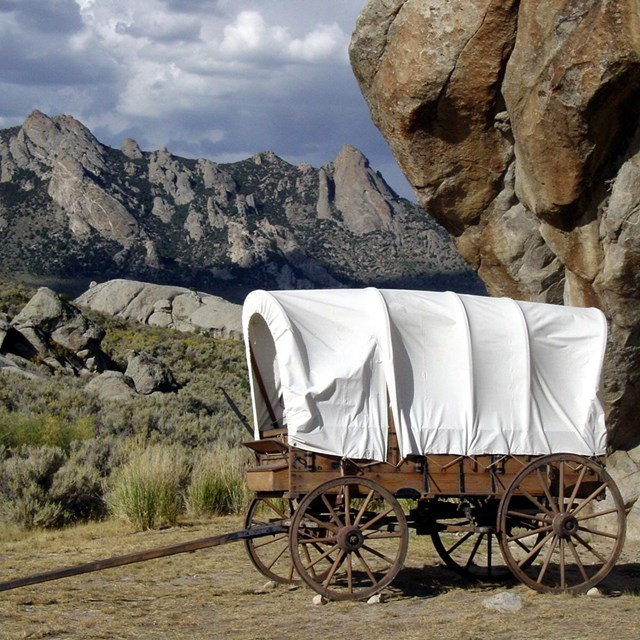 A covered wagon in front of a landscape of boulders and rocky outcroppings.