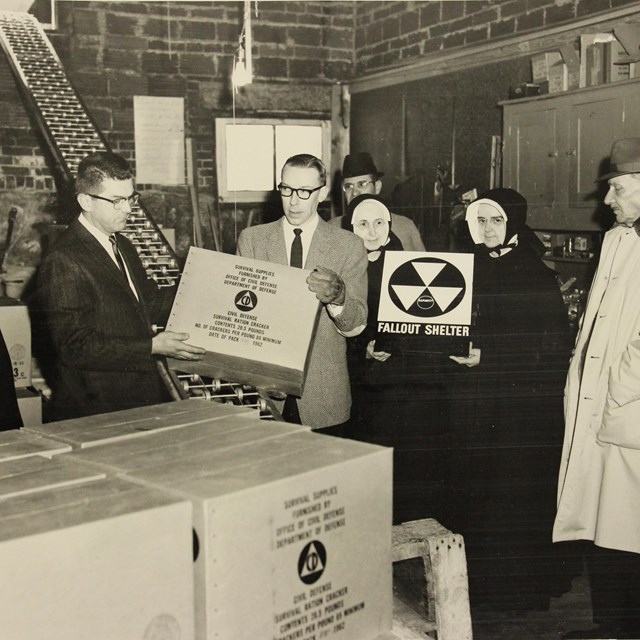 Period photograph of officials and nuns in a bomb shelter