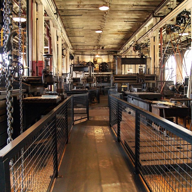 Metal fences guide you through a factory floor where machines driven by belts and chains wait.