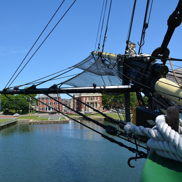 Bow of historic ship with buildings in background