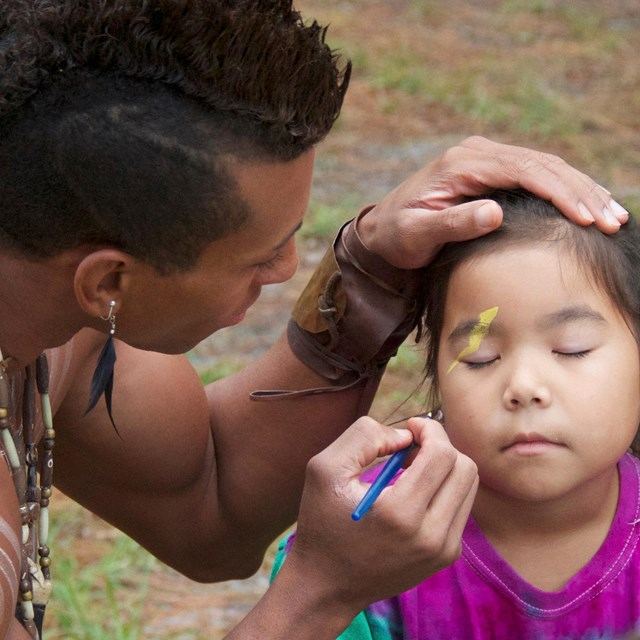 American Indian man paints the face of an American Indian girl.