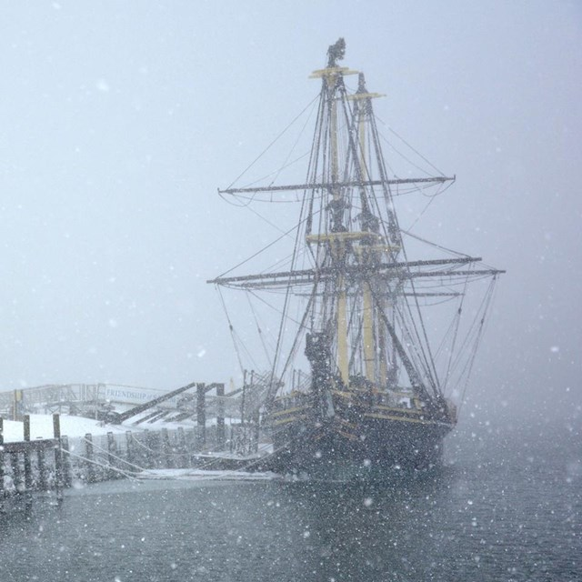 a winter scene in a port with a 3 masted ship