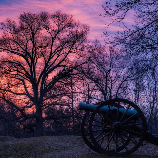 Canon on historic battlefield at sunset