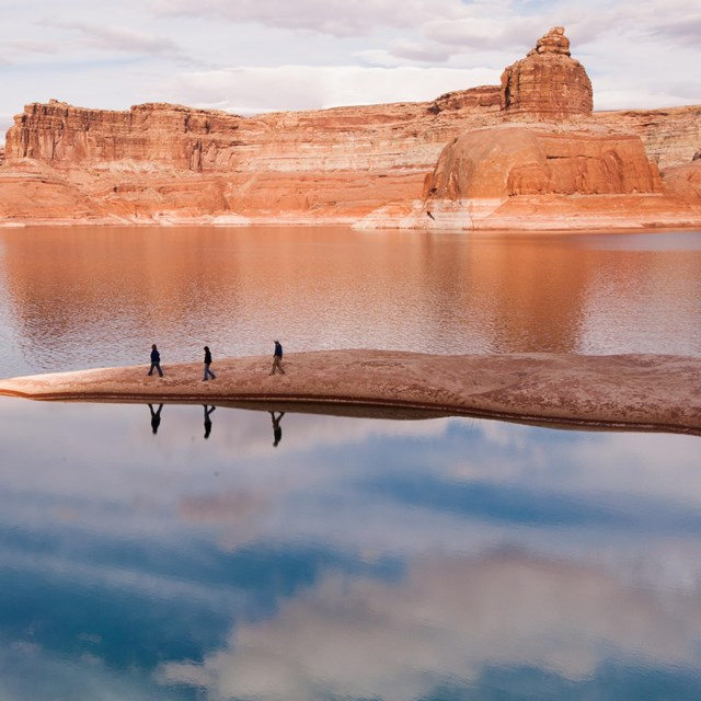 Three figures walk a thin rock outcropping surrounded by Lake Powell.
