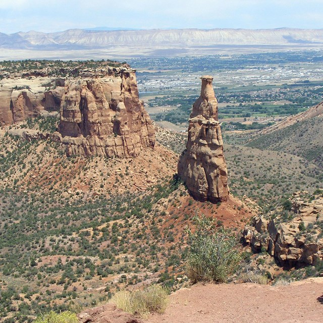 Independence Monument sandstone rock formation with the Grand Valley beyond.