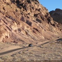 A vehicle drives along a single lane road through colorful, eroded hills.