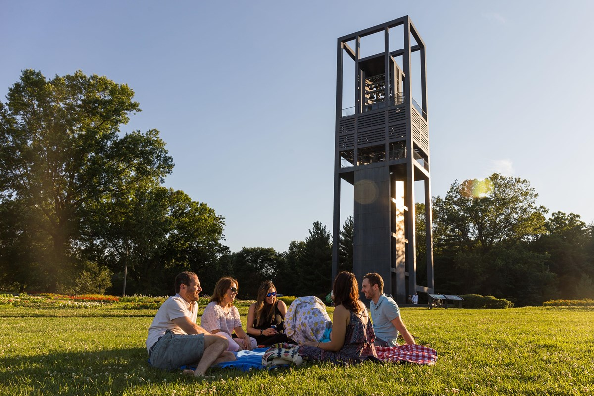 Visitors sitting under the Netherlands Carillon listen to the bells.