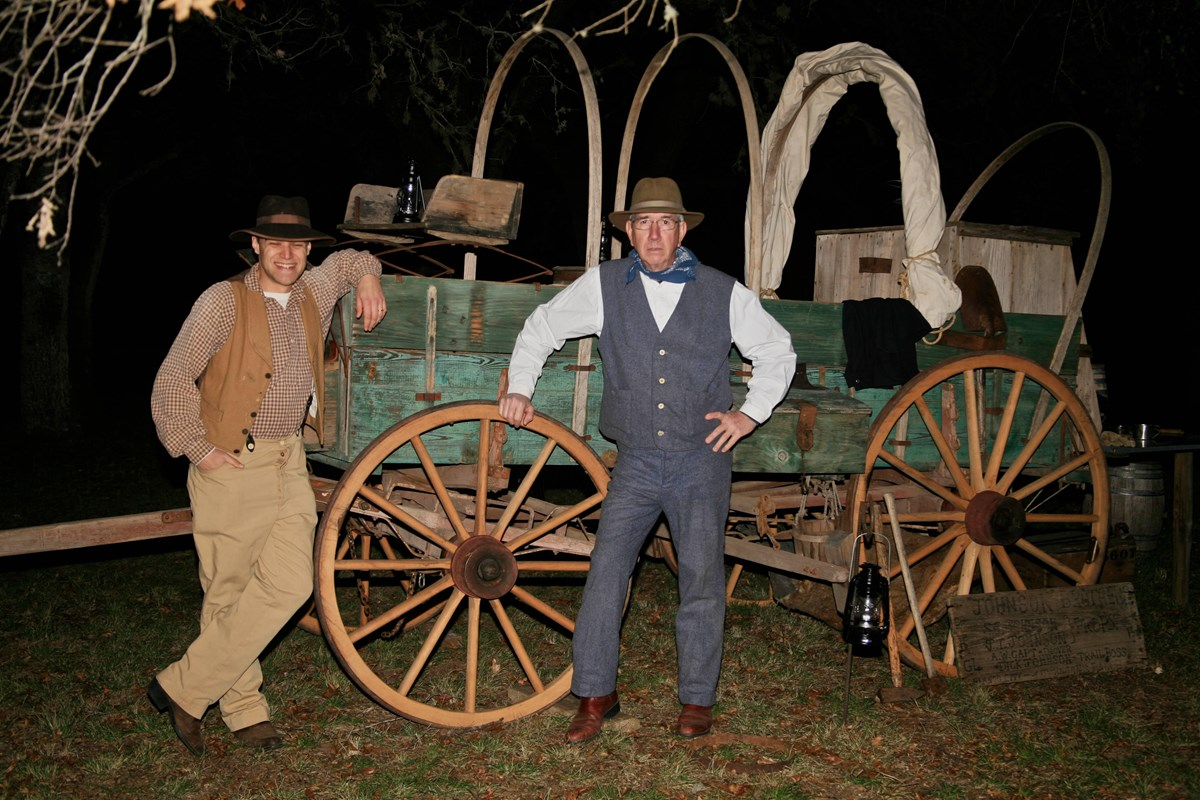 Cowboys dressed in 1860s attire stand next to a wooden chuckwagon.