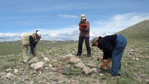 Three people bend over, measuring a rock grave, grassy hills, blue skies