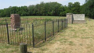 grass in foreground, fenced in cemetery, rock site identification sign: Santa Fe Trail