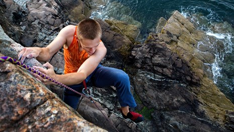 A young man scales a cliff