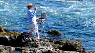Painter with small easel uses a smartphone to snap a photo up the coastline