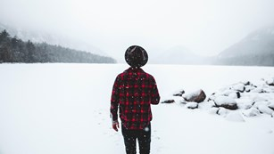 Man in hat and plaid jacket looks across frozen pond as snow falls